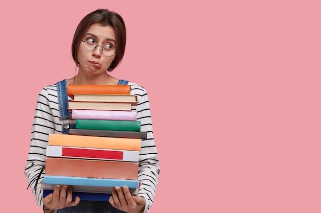 불만족스러운 백인 여자의 스튜디오 샷은 입술을 물고, 안경과 줄무늬 점퍼를 착용하고, 공부하고 싶지 않습니다.