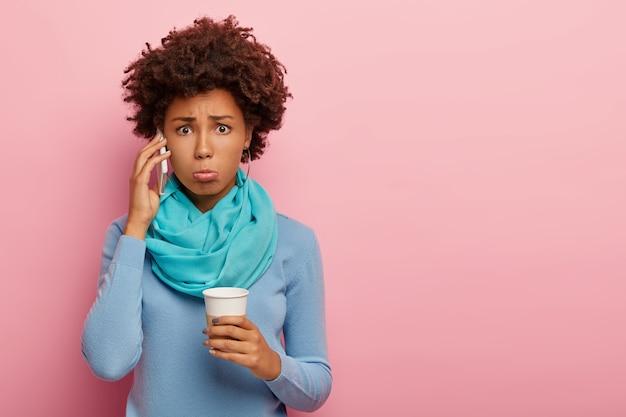 불만족 곱슬 여자의 스튜디오 샷 귀 근처에 휴대 전화를 보유하고, 불행한 표정을 놀라게하고, 커피를 마시고, 파란색 캐주얼 옷을 입고, 분홍색 배경에 포즈를 취합니다.