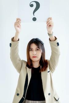 비즈니스 정장을 입은 의심스러운 여성 직원의 스튜디오 샷은 흰색 배경에 대한 답변에 대한 호기심을 보여주는 머리 위로 물음표 종이 판지 사인을 들고 있는 카메라를 쳐다봅니다.