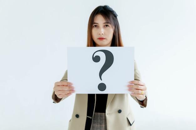 비즈니스 정장을 입은 의심스러운 여성 직원의 스튜디오 샷은 배경에 대한 답변에 대한 호기심을 보여주는 물음표 종이 마분지 기호를 들고 카메라를 봅니다.