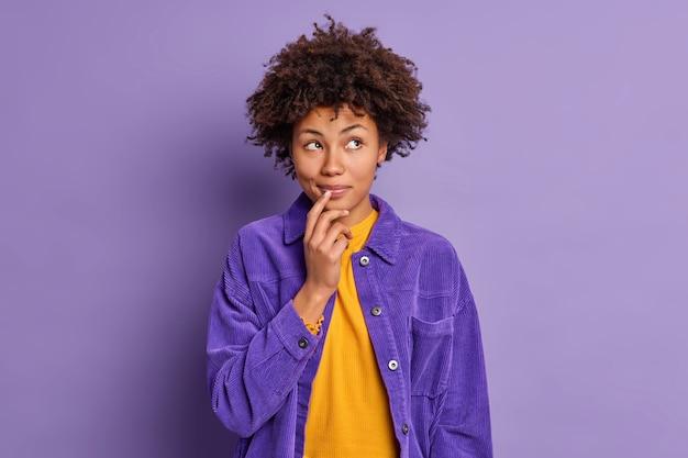 꿈꾸는 어두운 피부를 가진 젊은 여자의 스튜디오 샷은 세련된 보라색 재킷을 입고 신중하게 옆으로 보이는 입 근처에 손을 유지