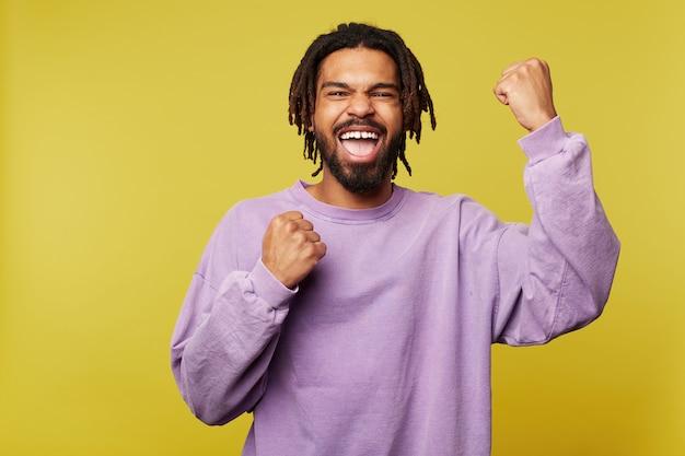 Студийный снимок эмоционального молодого довольно темнокожего бородатого мужчины с дредами, взволнованно поднимающего кулаки, стоя на желтом фоне в фиолетовой толстовке