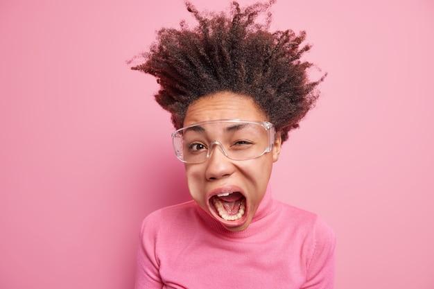感情的な狂った巻き毛のアフロアメリカ人女性のウィンクの目のスタジオショットは、口を大きく開いたままにして、透明なメガネのタートルネックを大声で身に着けていると叫びます