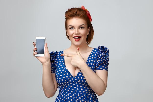 Студийный снимок эйфорической позитивной молодой домохозяйки в ретро-платье и с прической, эмоционально восклицающей: