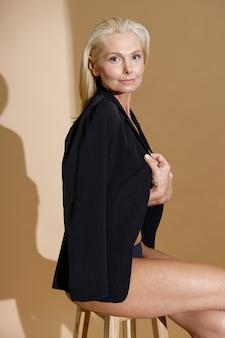 下着と上着の古典的な黒のジャケットでファッショナブルな成熟したブロンドの女性のスタジオショット