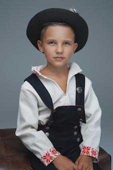 의자에 앉아 검은 모자와 흰색 옷을 입고 유행 어린 소년의 스튜디오 샷.