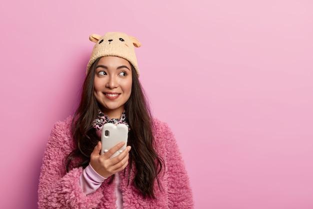 女性ブロガーのスタジオショットは、独自のwebブログを作成し、最新のセルラーを保持し、テクノロジーを使用し、積極的に脇を見て、テキストメッセージを読みます 無料写真