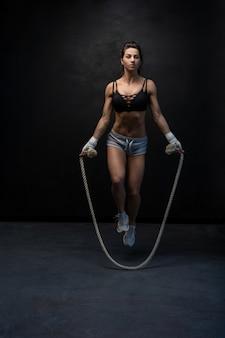 黒の上に縄跳びが立っているフィット感と筋肉質の女性のスタジオショット