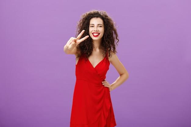 Студийный снимок дружелюбной шикарной и стильной молодой европейки с милой кудрявой прической и красными губами ...