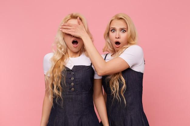 ピンクの背景に立っている間、口を大きく開いたままジーンズのドレスを着たおびえた長い髪のブロンドの女性のスタジオショット