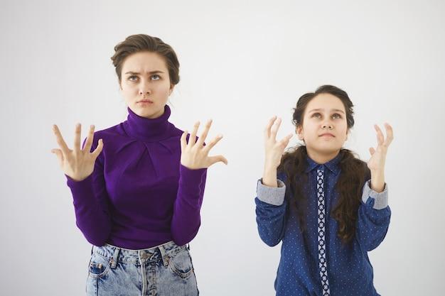 격렬한 자극을받은 십대 소녀와 그녀의 여동생이 흰 벽에 포즈를 취하는 스튜디오 샷, 감정적으로 몸짓, 화가 나서 올려다보기