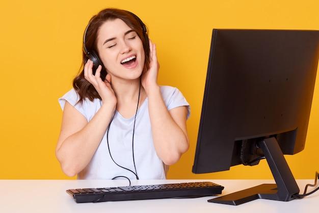 Студия выстрел девушка слушает музыку в наушниках и громко петь песни, сидя на белом столе перед персональным компьютером