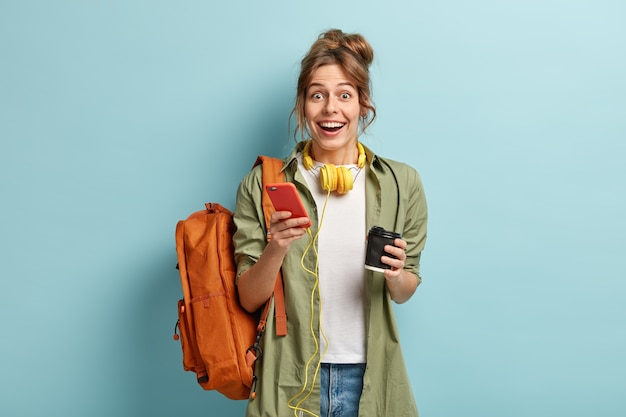 기쁜 힙 스터 소녀의 스튜디오 샷은 스테레오 헤드폰에 연결된 현대 휴대 전화를 보유하고 알림을 확인합니다.