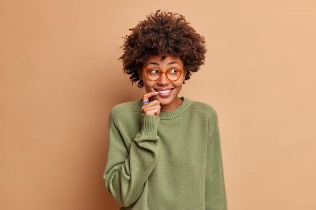 기쁜 여자의 스튜디오 샷은 호기심이 행복한 시선을 제쳐두고 손가락을 입술 근처에 유지하면서 베이지 색 벽 listnes 흥미로운 소문 위에 자연스럽게 고립 된 옷을 입고 미소 짓습니다.