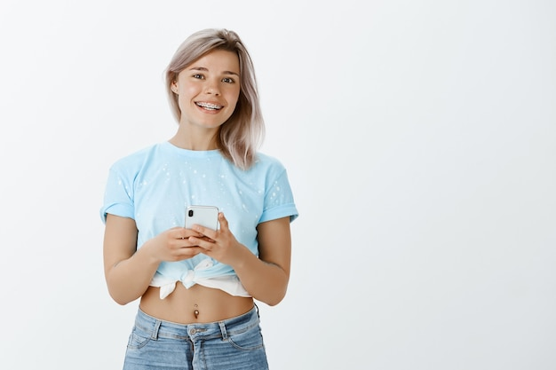 Студийный снимок красивой блондинки, позирующей со своим телефоном в студии