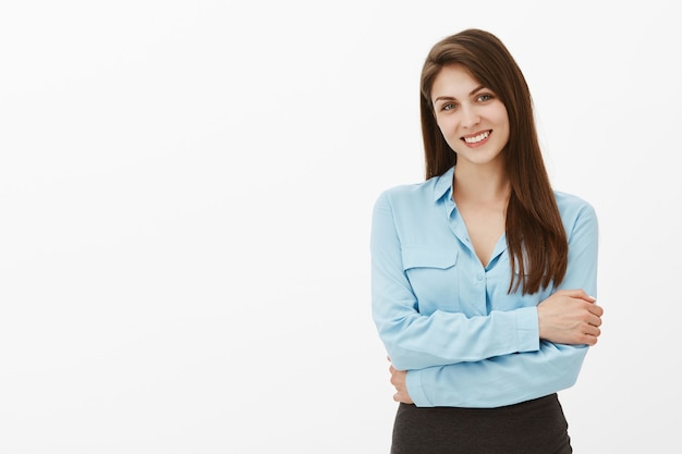Студийный снимок красивой брюнетки-бизнесвумен, позирующей в студии