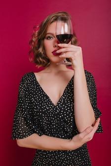 Студийный снимок красивой серьезной девушки, дегустирующей вино на вечеринке