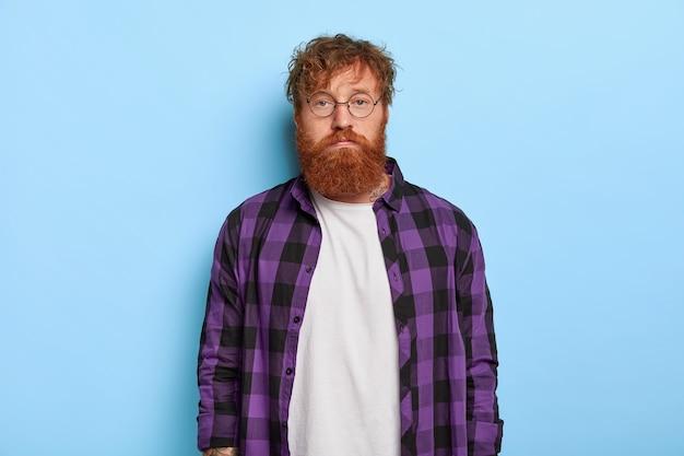 Студийный снимок симпатичного серьезного стильного рыжего парня, позирующего на фоне синей стены