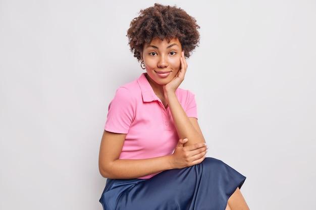 곱슬머리를 한 잘 생긴 여성의 스튜디오 샷은 분홍색 티셔츠와 치마를 입고 흰 벽에 옆으로 포즈를 취하고 있다