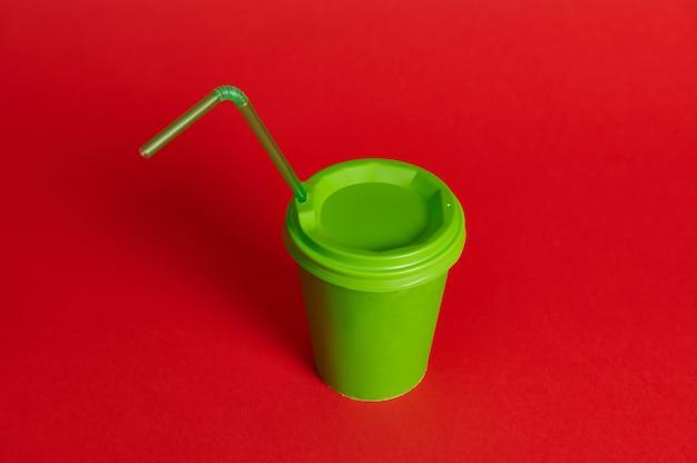 Студия сняла зеленую бумажную кружку на вынос с соломой на красном фоне. скопируйте пространство. цветовой контраст