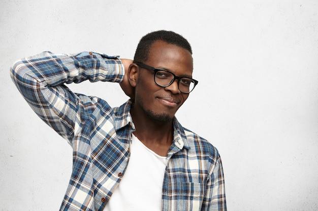 トレンディな眼鏡をかけているハンサムなアフリカ系アメリカ人のヒップスターのスタジオ撮影