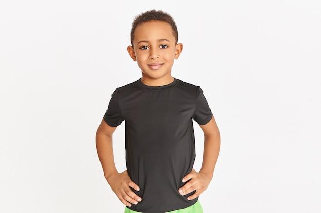 腰に手を置いて、屋内でトレーニングしている黒いtシャツで孤立してポーズをとっているハンサムな運動の暗い肌の小さな男の子のスタジオショット。