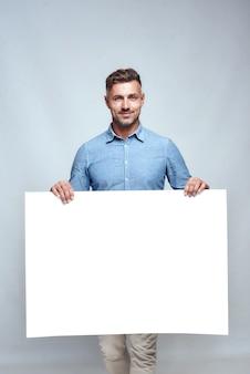 Студия выстрел красивый бородатый мужчина в повседневной одежде, держа пустую пустую доску и улыбаясь, стоя на сером фоне. реклама