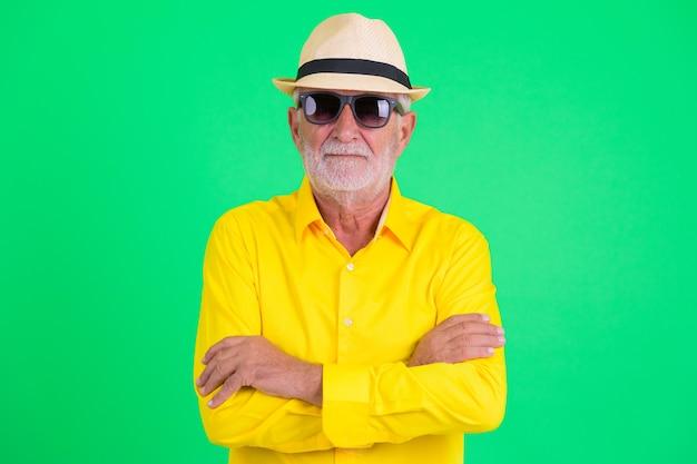 緑の背景にハンサムなひげを生やしたシニア観光男性のスタジオショット