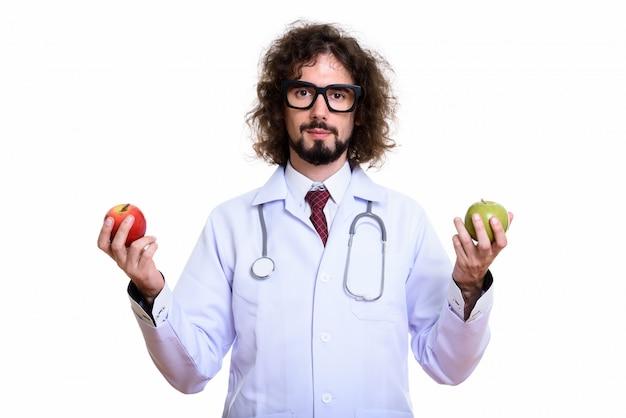 赤いリンゴと緑を保持しているハンサムな男性医師のスタジオ撮影、