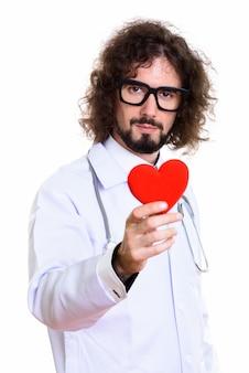赤いハートを保持しているハンサムな男医師のスタジオ撮影