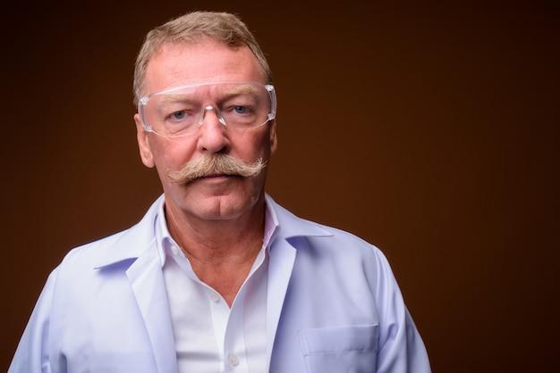 Студийный снимок красивого старшего мужчины-доктора с усами в защитных очках от коричневого