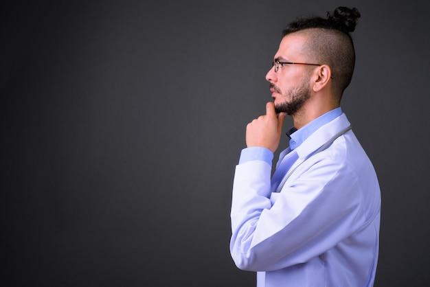 灰色の背景に対してハンサムなトルコ人医師のスタジオショット