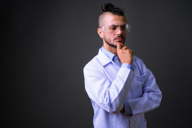 灰色の背景に対して保護メガネをかけているハンサムなトルコ人医師のスタジオショット
