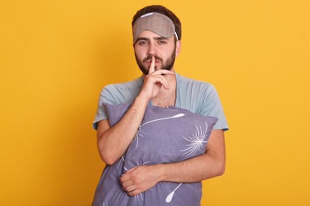Студия выстрел красивый с бородой человек, стоящий на желтой стене студии