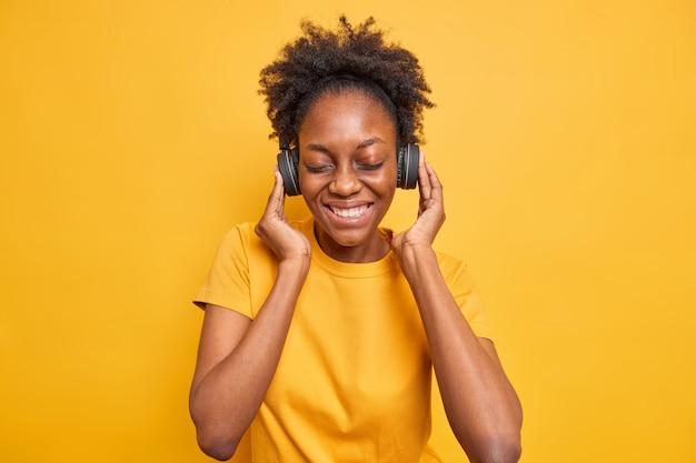 幸せなアフリカ系アメリカ人の10代の少女のスタジオショットは、ヘッドフォンを手に保ち、完璧な音質を楽しんでいます。鮮やかな黄色で隔離されたカジュアルなtシャツを着て目を閉じて笑顔
