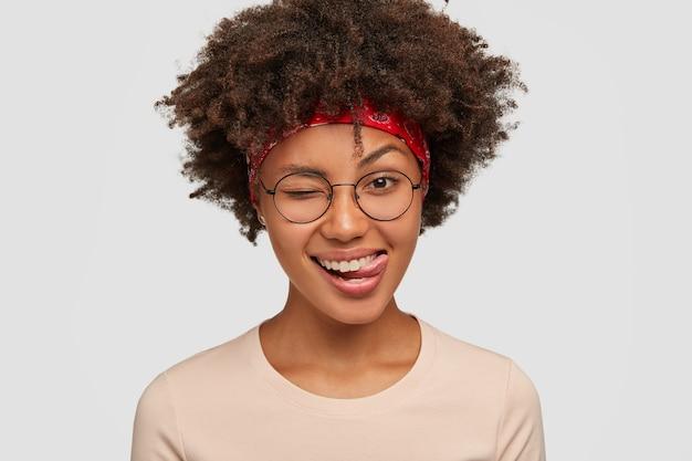 幸せな黒人の女の子のスタジオショットは屋内で楽しんでいます