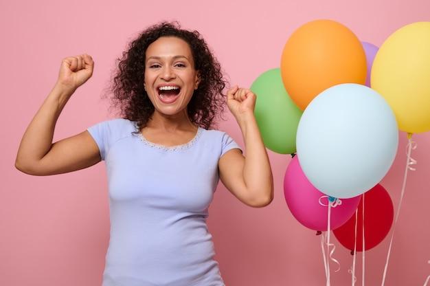 幸せなのんきな女性のスタジオショットは踊り、青いシャツとデニムのショートパンツを着て楽しんで、お祭り気分で、膨らんだ風船でピンクの背景にポーズをとるパーティーを開くための時間の概念。
