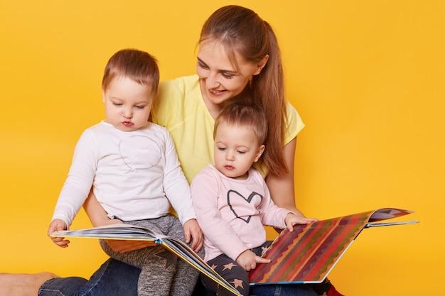행복 한 가족의 스튜디오 샷입니다. 엄마와 작은 쌍둥이 소녀, 바닥에 앉아 책을 읽고 밝고 재미있는 사진을보고, 엄마와 함께 시간을 보내고