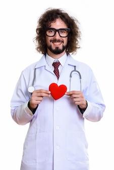 赤いハートを持って笑って幸せな男医師のスタジオ撮影