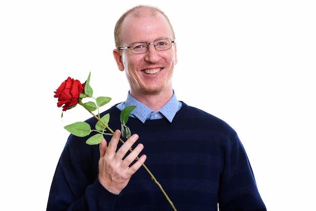 Студийный снимок счастливого человека, улыбающегося, держа красную розу
