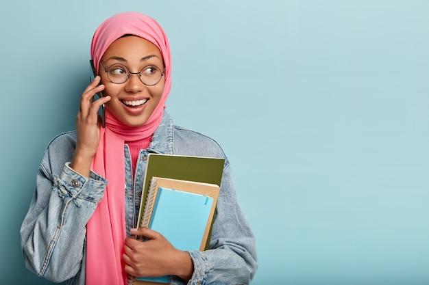 행복한 긍정적 인 여성의 스튜디오 샷은 이슬람 종교적 견해를 가지고 있으며 스마트 폰으로 무언가를 토론합니다.