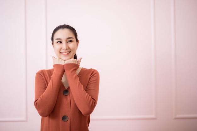 밝은 오렌지색 니트 점퍼를 입은 행복한 낙관적인 아시아 여성의 스튜디오 샷