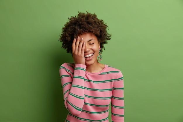 幸せな女性のスタジオショットは、顔の手のひらを広く笑顔にします明るい緑の壁に隔離されたカジュアルなストライプのジャンパーに身を包んだ非常に面白いものを大声で笑って楽しんでいます
