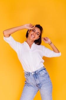 노란색 벽에 포즈 흰 셔츠와 데님 바지를 입고 행복한 여자 짧은 머리의 스튜디오 샷