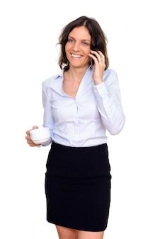 Студийный снимок счастливой женщины разговаривает по мобильному телефону, держа чашку кофе, изолированную на белом фоне