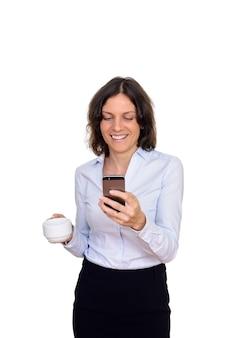 Студийный снимок счастливой женщины, использующей мобильный телефон, держа чашку кофе, изолированную на белом фоне
