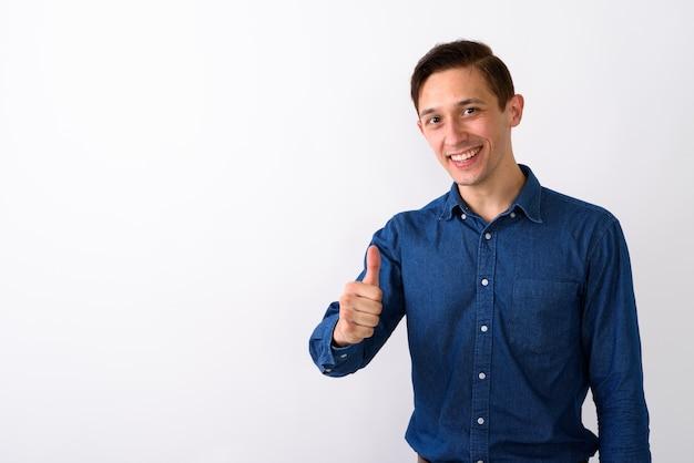 幸せな若いハンサムな男の笑顔と手を与えるスタジオショット