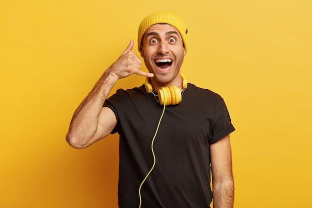 Студийный снимок счастливого молодого человека делает жест звонка, широко улыбается, просит позвонить ему