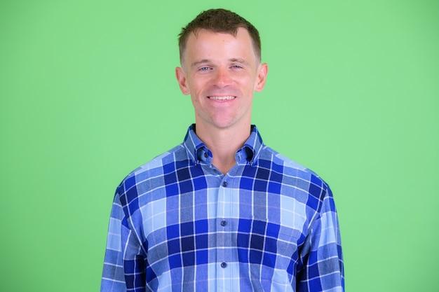 緑の背景に青い市松模様のシャツを着ている流行に敏感な男のスタジオショット