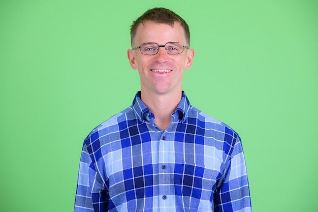 녹색 배경에 안경을 쓰고 힙 스터 남자의 스튜디오 샷